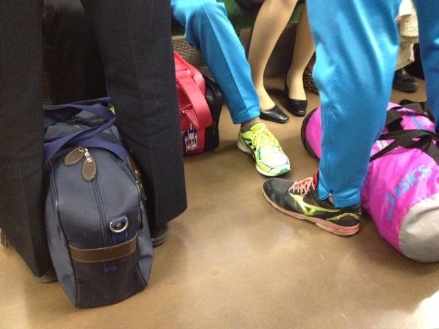 電車で足元に荷物を置いている人