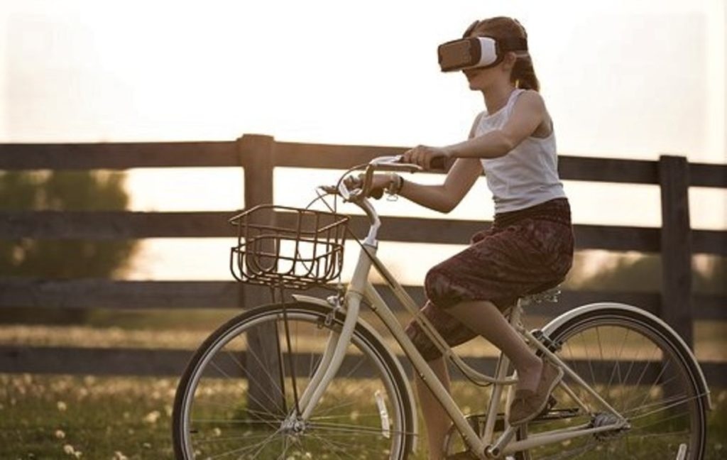 自転車に乗りながらイヤホンをしてスマホを弄っている人