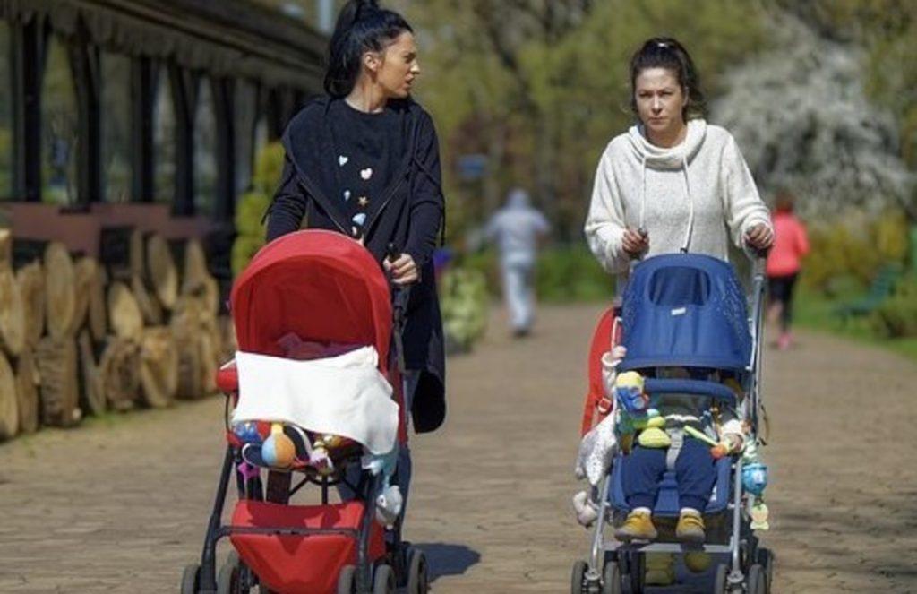 ベビーカーを押しながら歩きスマホをしている母親